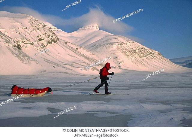 Ski tourer hauling sledge on spring traverse Ny Alesund to Longyearbyen Spitsbergen Island Svalbard Norwegian Arctic