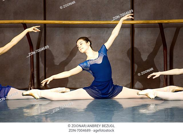 Young ballerina on the lesson of classical choreography sitting in the splits gracefully raising his hands up near barre