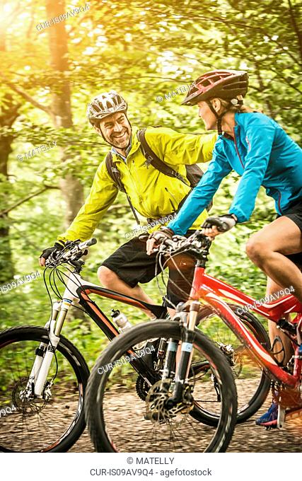 Mature mountain biking couple chatting and cycling along rural forest trail