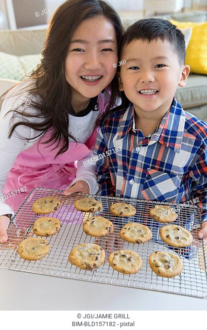 Asian brother and sister baking cookies