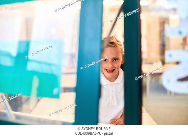 Portrait of schoolgirl looking through classroom window at primary school