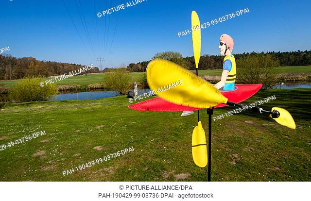 19 April 2019, Lower Saxony, Bienenbüttel: A toy canoe which moves through the wind stands on the bank of the Ilmenau. In the future there will be a time out...