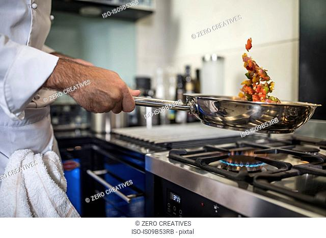 Chef holding frying pan, cooking food over stove, close-up