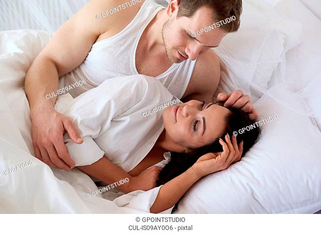 Young man waking girlfriend in bed