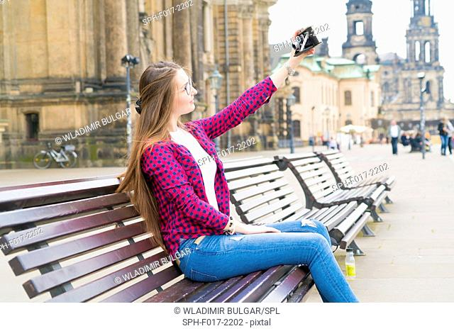 MODEL RELEASED. Young woman taking photo of herself with camera, Dresden, Germany