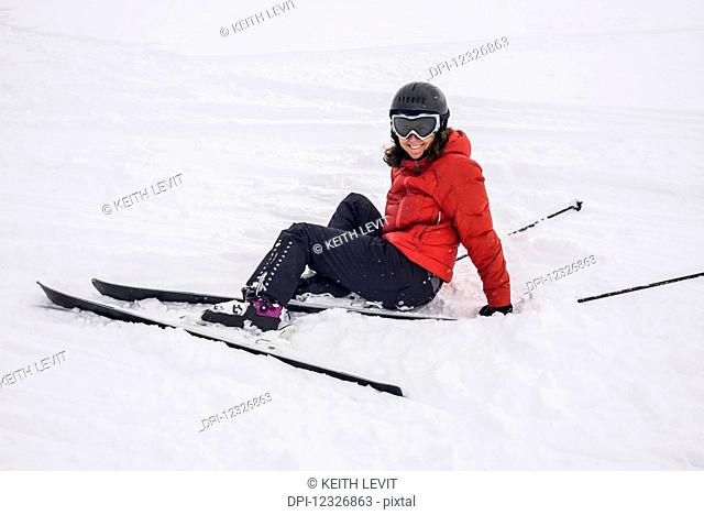 A skier in a red coat sitting in the snow; Whistler, British Columbia, Canada