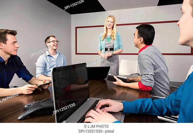 Young millennial businesswoman giving a presentation to other business professionals working in a conference room in a modern place of business; Sherwood Park