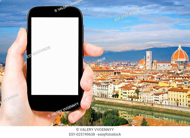 travel concept - hand holds smartphone with cut out screen and Florence skyline on background