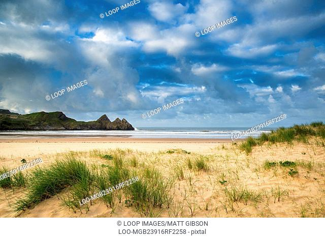 Beautiful morning landscape over sandy beach Three Cliffs Bay