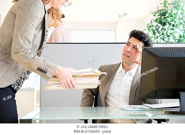 Businesswoman giving colleague stack of papers