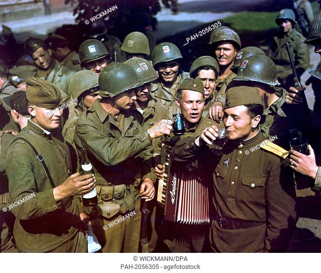 Soviet and American (with helmets) soldiers raise their glasses on the occasion of their historic meeting at the river Elbe