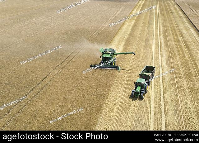 01 July 2020, Hessen, Frankfurt/Main: A farmer with a combine harvests winter barley (aerial view with a drone). The harvesting season has officially begun in...