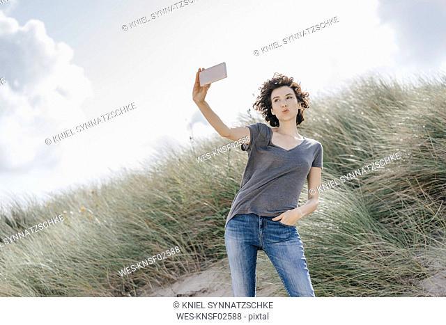 Woman standing in beach dune taking a selfie