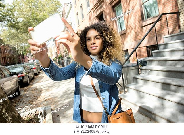Mixed Race woman in city posing for cell phone selfie