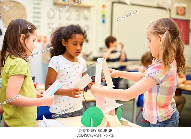 Three primary schoolgirls making paper pyramid in classroom