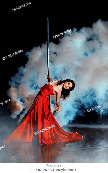 Girl shrouded in smoke dancing around a pole dance. See more images from this series