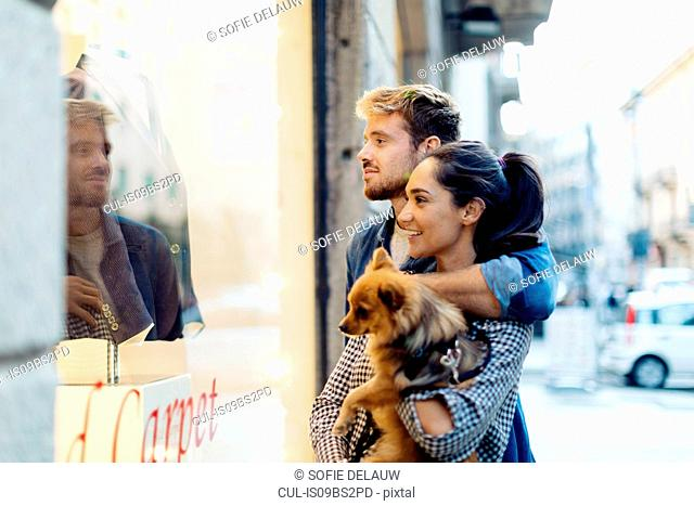 Couple with pet dog window-shopping, Milan, Italy