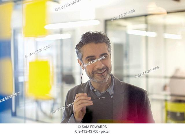Confident, smiling creative businessman brainstorming in office