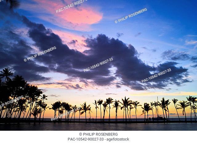 Hawaii, Big Island, Anaeho'omalu Bay Fish Pond, Sunset silhouettes a line of palm trees