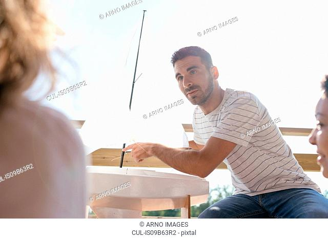 Man talking through sailing boat parts, to two women at nautical club