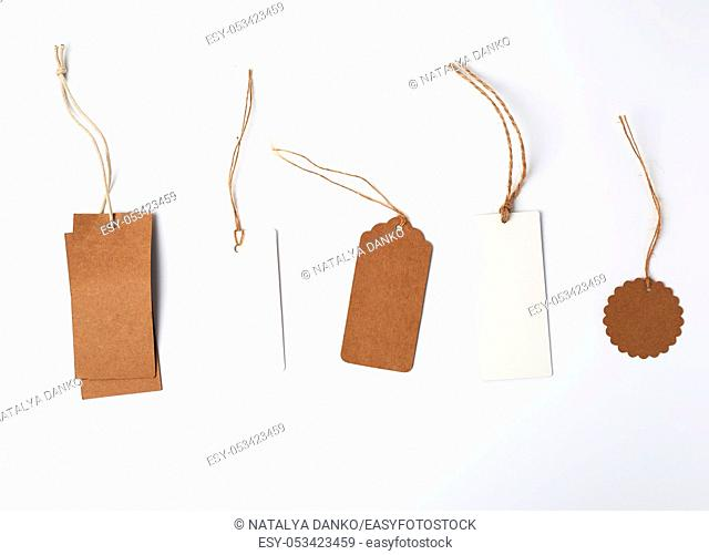 round and rectangular price tags from brown and white paper hang on a rope, white background