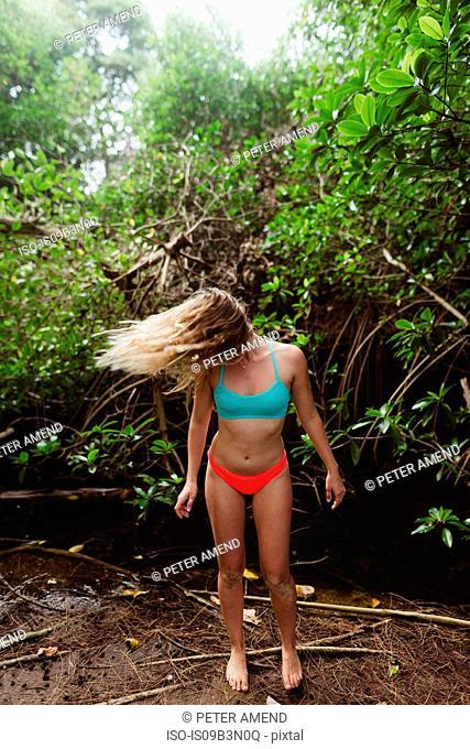 Young woman wearing bikini in forest throwing hair back, Oahu, Hawaii, USA