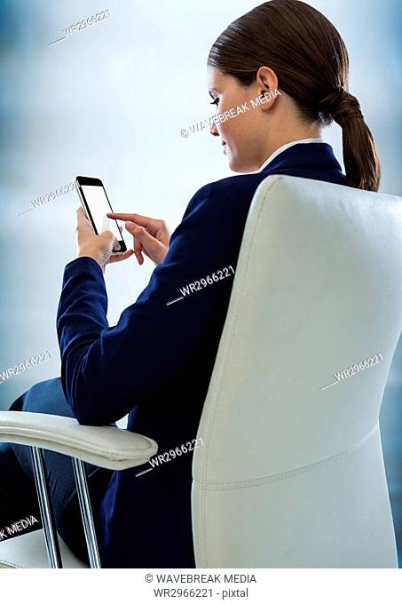 Seated business woman with phone against blurry blue wood panel