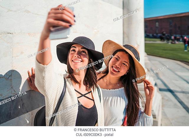 Friends taking selfie in front of building