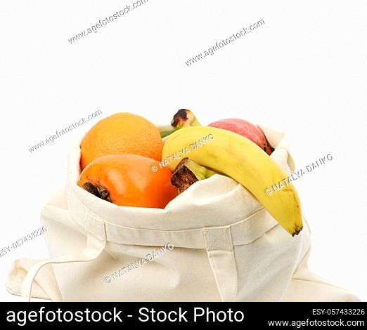 beige textile bag with fresh fruits on a white background, zero wast