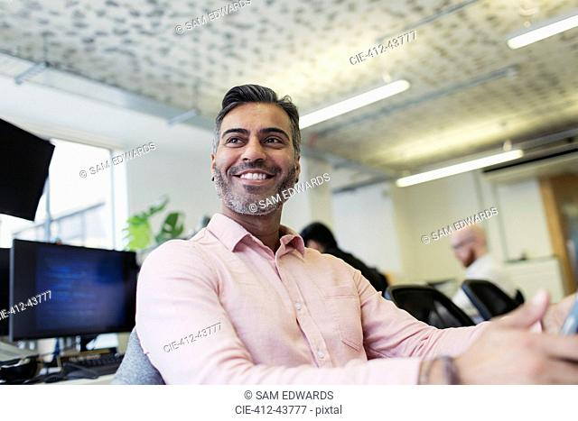 Smiling, confident businessman working in office