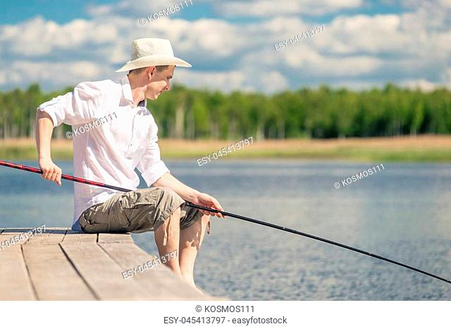male fisherman with a fishing rod sits on the pier near the lake