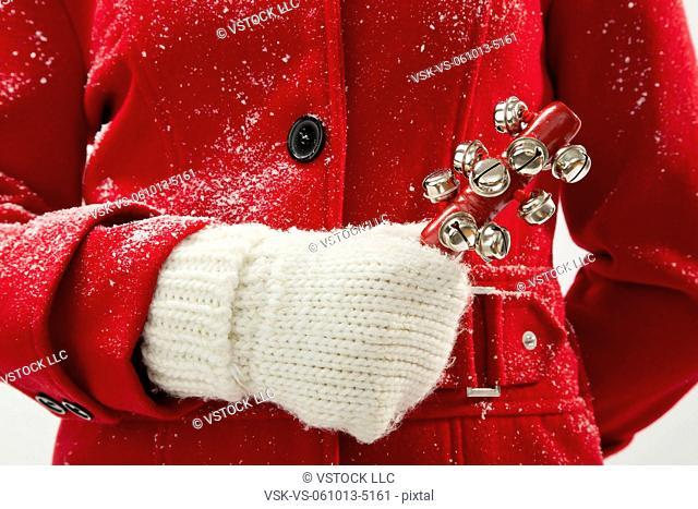 Girl (12-13) holding jingle bells