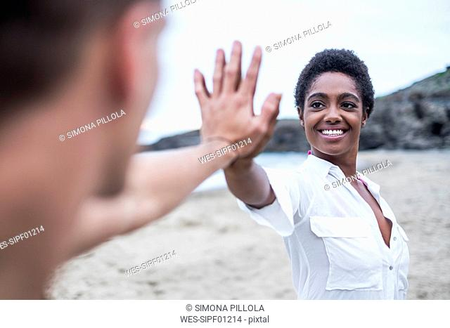 Young couple connecting their hands on the beach