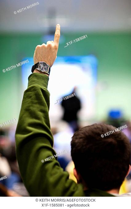 Rear view of a young man holding his hand up to ask a question in a meeting, UK