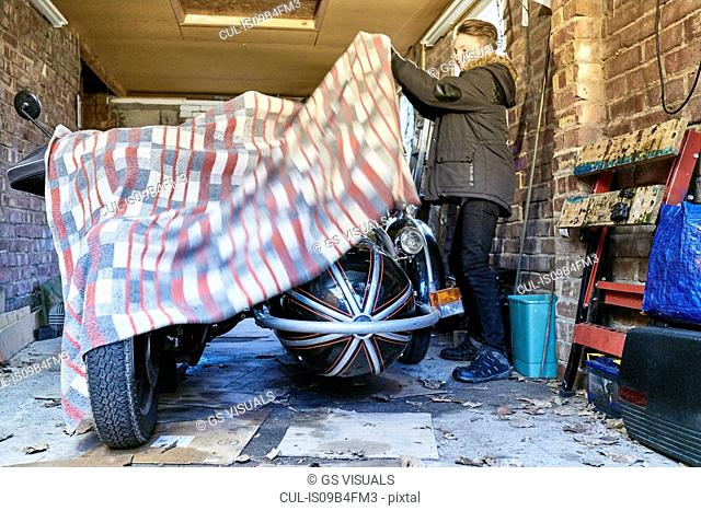 Boy removing blanket from motorcycle and sidecar in garage