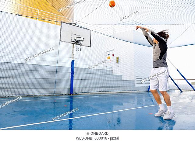Young man playing basketball on a deck of a cruise ship