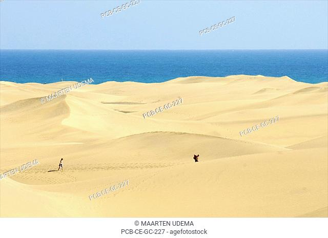 Two people taking a hike in the dunes at Playa de Maspalomas