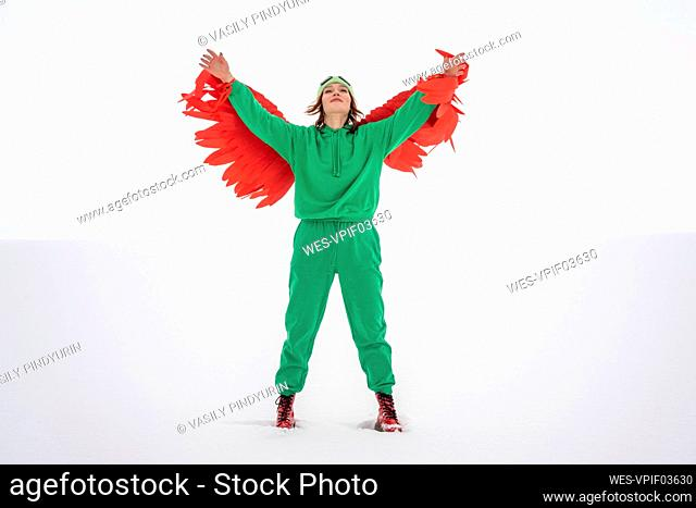 Carefree woman in green bird costume raising arms while standing on snow against sky