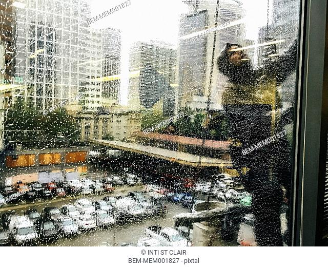 Window washer cleaning rainy window of office building