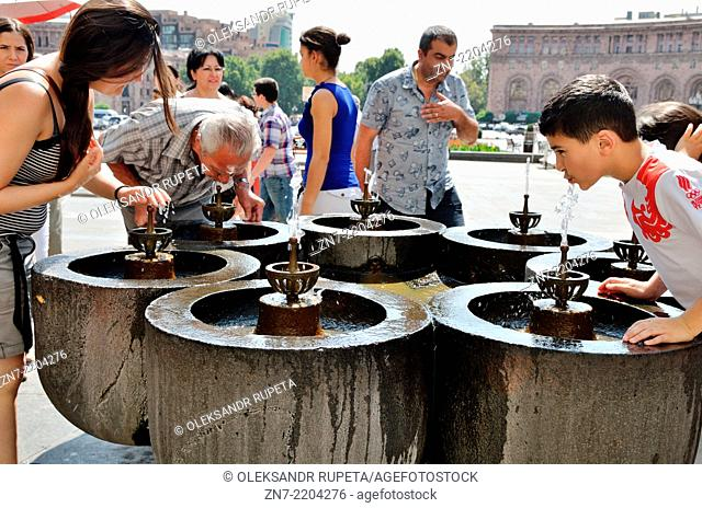 A group of people take a drink from Yerevan's natural drinking water fountains, Armenia