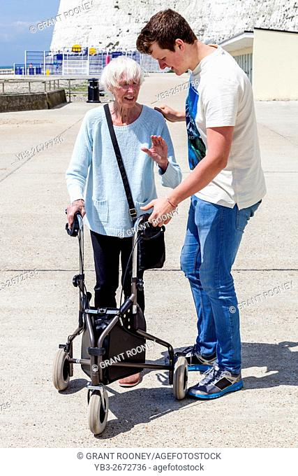 An Elderly Disabled Woman Using A Rollator Walking Aid Helped By Her Grandson, Brighton, Sussex, UK
