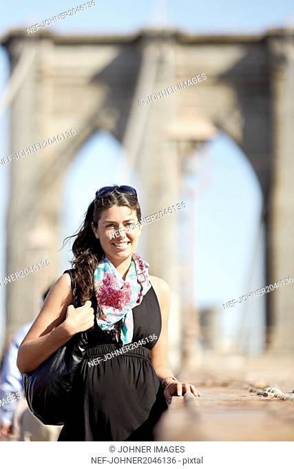 Woman in black dress with Brooklyn Bridge in background
