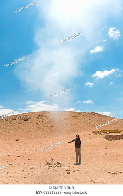 Woman touches hot steam at Sol de Manana geothermal field in Bolivia