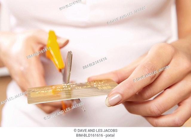 Caucasian woman cutting credit card