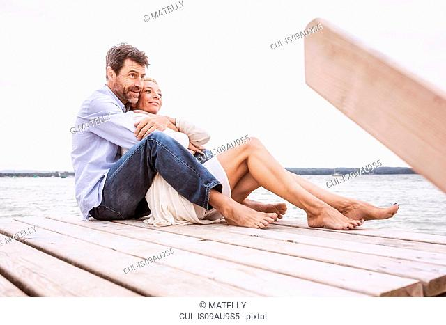 Mature couple sitting, hugging, on pier