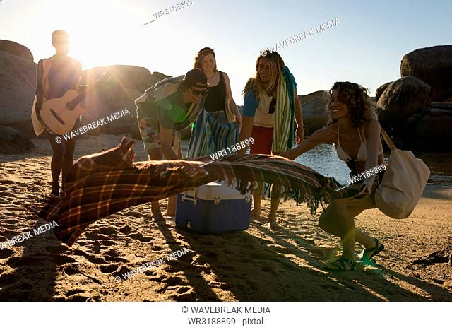 Group of friends laying down picnic blanket