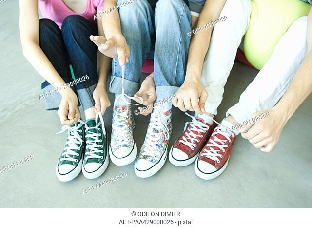 Friends sitting on floor, wearing canvas shoes, tying laces, low section