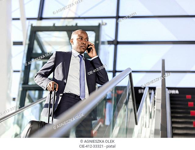 Businessman talking on cell phone on airport escalator