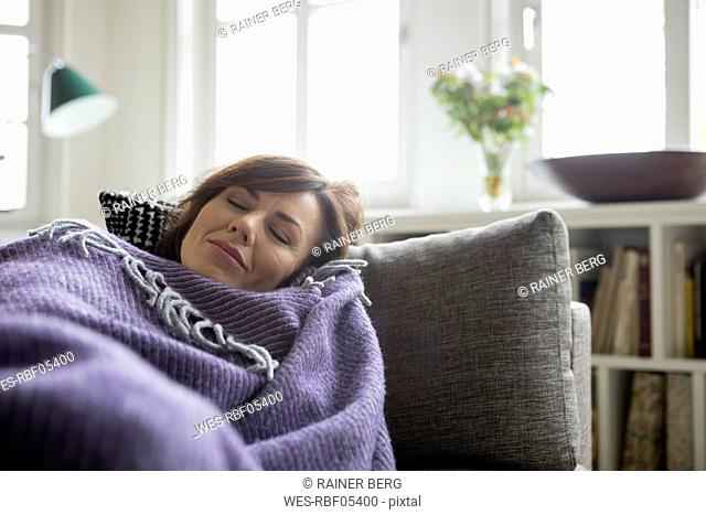 Woman with blanket lying on the sofa