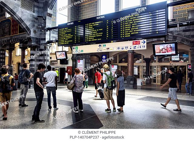 Travelers looking at timetable in departure hall of the Gent-Sint-Pieters / Saint Peter's railway station in Ghent, East Flanders, Belgium